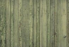 Alter hölzerner grüner Zaun für Hintergrund von den Brettern von verschiedenen Breiten stockbild