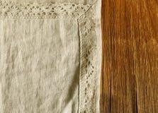 Alter hölzerner Hintergrund mit Leinenspitzeserviette stockbild