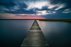 Alter hölzerner Pier auf ruhigem See bei Sonnenuntergang Stockfoto
