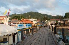 Alter hölzerner Pier und Boote im Hafen lizenzfreie stockfotos