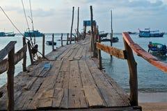 Alter hölzerner Pier und Boote im Meer stockfotografie