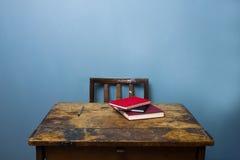 Alter hölzerner Schreibtisch und Stuhl mit Büchern und einem Stift Lizenzfreies Stockbild