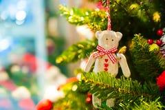Alter hölzerner Spielzeugbär mit einem roten Bogenband, das an Weihnachtsbaum im Hintergrund andere Dekorationen und Girlanden hä Lizenzfreies Stockfoto