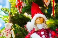Alter hölzerner Spielzeugbär mit einem roten Bogenband, das am Weihnachtstannen-Baum hängt, spielt brennende Kerzen, Kästen, Bäll Stockbild
