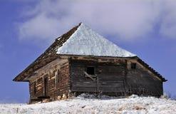 Alter hölzerner Stall mit Schnee auf dem Dach Stockfoto