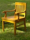 Alter hölzerner Stuhl auf dem Gras Stockfotografie