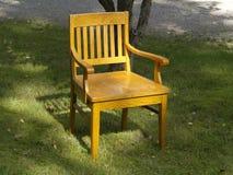 Alter hölzerner Stuhl auf dem Gras Stockbild