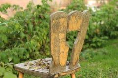 Alter hölzerner Stuhl im grünen Garten Lizenzfreies Stockbild