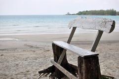 Alter hölzerner Stuhl am Strand Stockbild