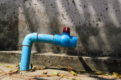 Alter Hahn im Freien mit blauem Rohr auf Wand Lizenzfreie Stockbilder