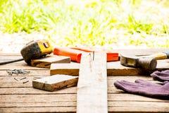 Alter Hammer des Hintergrund-Handwerkerwerkzeugs mit Maßband und kleinen Nägeln und Ansicht der Säge und des Arbeitens im Freien  Stockfotografie