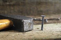 Alter Hammer mit einem alten Nagel lizenzfreie stockfotografie
