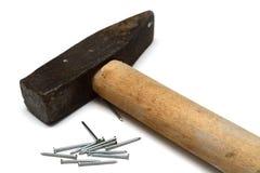 Alter Hammer mit einem Holzgriff und Nägeln Lizenzfreie Stockbilder