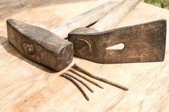 Alter Hammer, Queraxt und rostige Nägel Stockbilder