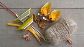 Alter heiliger Thread, Kerze, Räucherstäbchen, Josspapier und trockene Blume auf dem Bretterboden Lizenzfreie Stockfotos