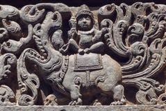 Alter hindischer Gott, der auf Mythos- Löwegeschöpf, sculpured Steinentlastung Carvings von Tempel ` s Wand, Indien sitzt Stockfoto