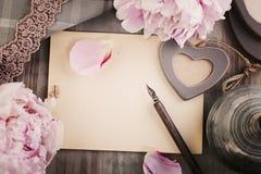 Alter Hintergrund des leeren Papiers mit Blumen, Liebes-Herzen, Stift und Gummilack Lizenzfreie Stockfotos