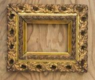 Alter hölzerner aufwändiger Bilderrahmen auf hölzernem Hintergrund Stockbild