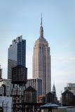 Alter hölzerner Wasserspeicher ragt in Nebeneinanderstellung mit modernen Wolkenkratzern wie Empire State Building hoch Stockbild