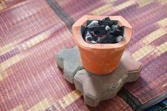 Alter Holzkohlenofen mit der angezündeten Holzkohle bereiten sich für das Kochen vor Stockbild