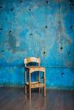 Alter Holzstuhl im Schmutzraum mit blauer Wand Lizenzfreie Stockbilder