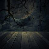 Alter Holztisch über totem Baum, Halloween-Hintergrund Lizenzfreie Stockfotos