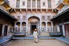 Alter indischer Mann tritt vom alten Palast Stockbild