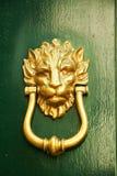 Alter italienischer Löweform-Türklopfer auf grünem Holz Lizenzfreie Stockbilder