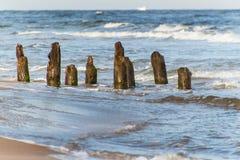 Alter Küstenschutz mit einem Wellenbrecher Hölzerne Stangen im Meer Herbstmorgen auf dem Strand der Ostsee Lizenzfreie Stockfotografie
