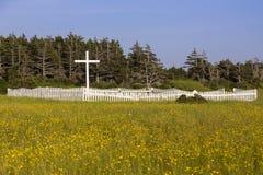 Alter katholischer Kirchhof mit weißem hölzernem Kreuz und Palisadenzaun auf einem Gebiet von gelben Wildflowers lizenzfreie stockfotografie
