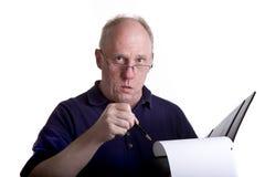 Alter Kerl, der auf Problem im Notizbuch zeigt Lizenzfreie Stockbilder