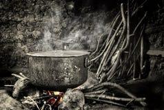 Alter Kessel, der auf heißem Feuer sitzt Lizenzfreies Stockfoto