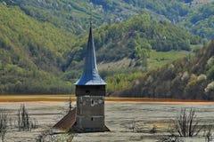 Alter Kirchturm in verseuchtem See stockfotografie