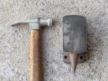 Alter kleiner Hammer und Miniaturamboß mit konkretem Hintergrund Lizenzfreie Stockbilder