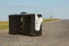 Alter Koffer mit Geld und Handschellen Stockfotografie