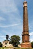Alter Kohlenminenschacht mit einem Bergbauturm im hohen Kamin des Vordergrunds Lizenzfreie Stockfotos