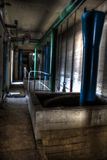 Alter Korridor mit den blauen und grünen Rohren Stockfotografie