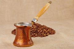 Alter kupferner Kaffepotentiometer und Kaffeebohnen auf Segeltuchhintergrund. Lizenzfreie Stockfotos