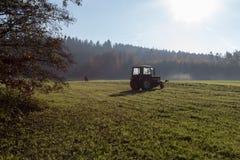 alter Landwirt, der Gras harkt Lizenzfreie Stockfotos