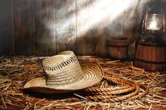 Alter Landwirt-Hut und Ranching-Seil im antiken Stall Stockfotos