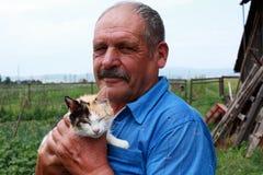 Alter Landwirt mit einer farbigen Katze Stockfotografie