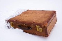 Alter lederner brauner Koffer im Schnee lizenzfreies stockfoto