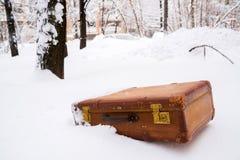 Alter lederner brauner Koffer im Schnee lizenzfreies stockbild