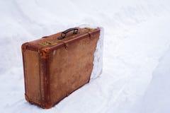 Alter lederner brauner Koffer im Schnee stockfotos