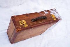 Alter lederner brauner Koffer im Schnee lizenzfreie stockfotos