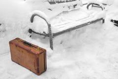 Alter lederner brauner Koffer steht im Schnee nahe der Bank stockfotografie