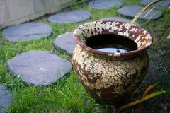 Alter Lehmvase mit Wasser im Hofgarten Stockbild