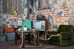 Alter Lehnsessel, Fernsehen, Radio und Tabelle mit Samowar Stockbild