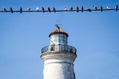 Alter Leuchtturm mit Vögeln auf Draht Lizenzfreies Stockfoto