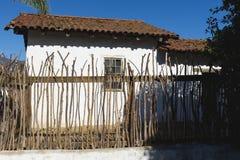 Alter luftgetrockneter Ziegelstein und ein hölzerner Zaun Stockfoto
